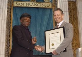 במהלך האירוע, ראש עיריית סן-פרנסיסקו, וילי בראון (משמאל) העניק לארגון הסיינטולוגיה הכרזה שמציינת לשבח את הארגון על